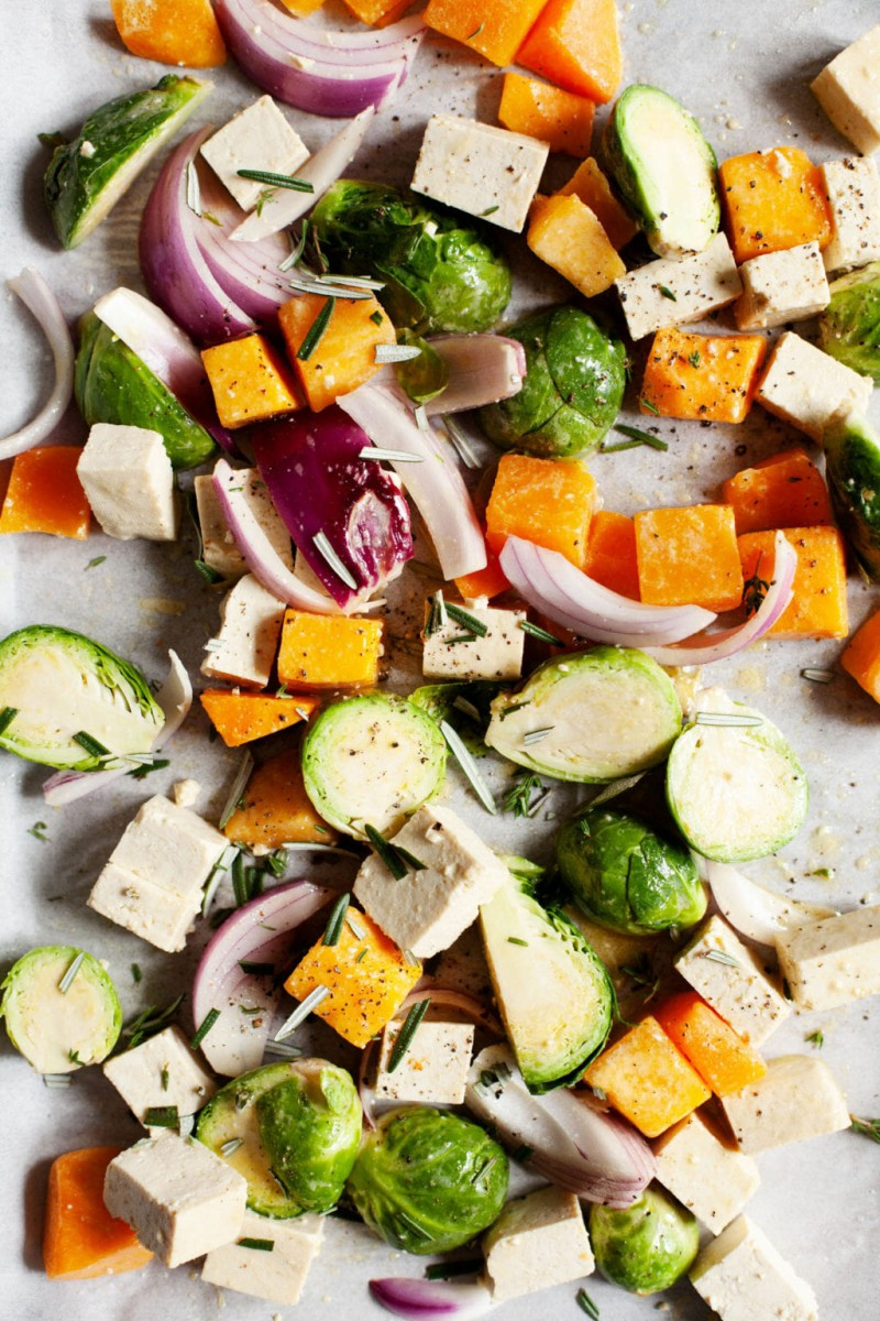 A sheet pan covered with autumn vegetables and tofu, ready for baking.