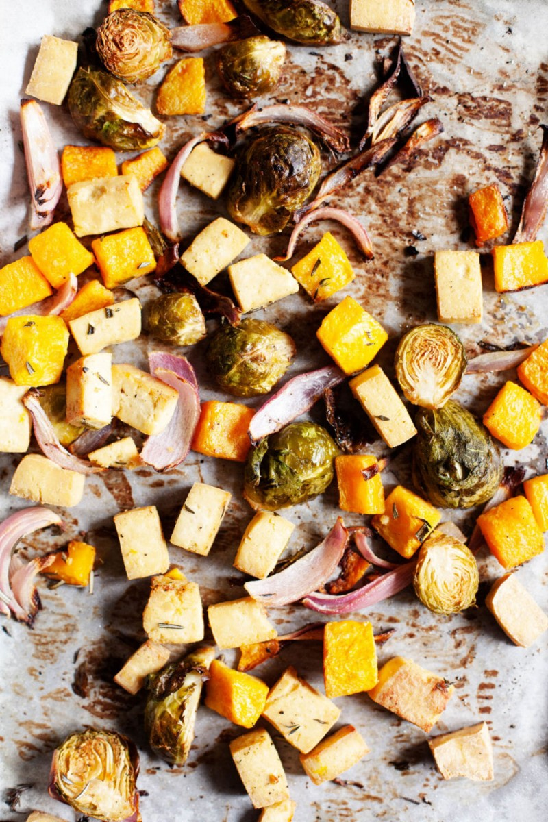 A baking sheet is covered with freshly roasted autumn produce and herbs.